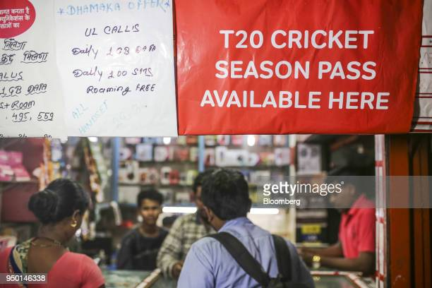 An advertisement for Bharti Airtel Ltd is dispalyed above customers at a sim card store in Mumbai India on Saturday April 21 2018 Bharti Airtel are...