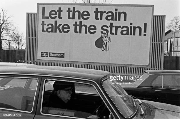 An advertisement for British Rail's Southern Region reading 'Let The Train Take The Strain' beside a traffic jam on the Old Kent Road in London, UK,...