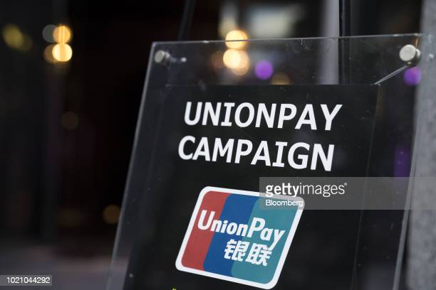 An advertisement for China UnionPay Co logo is displayed outside a luxury store in Tokyo Japan on Tuesday Aug 21 2018 Japan is scheduled to release...