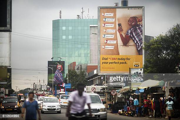 An advertisement for MTN Group Ltd mobile communications sits on a roadside above street vendors' stalls in Accra Ghana on Tuesday Sept 20 2016...
