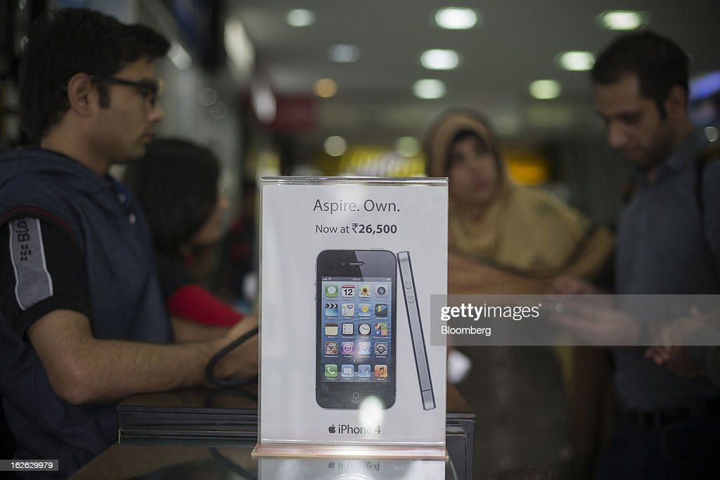 An advertisement for the Apple Inc. iPhone 4 is displayed in a store in Connaught Place in New Delhi, India, on Saturday, Feb. 23, 2013. Finance Minister Palaniappan Chidambaram, who will present his annual budget to parliament on Feb. 28, will seek to narrow the shortfall to 4.8 percent of gross domestic product in the year starting April, from this year's goal of 5.3 percent, according to a Bloomberg survey of analysts and investors. Photographer: Brent Lewin/Bloomberg via Getty Images