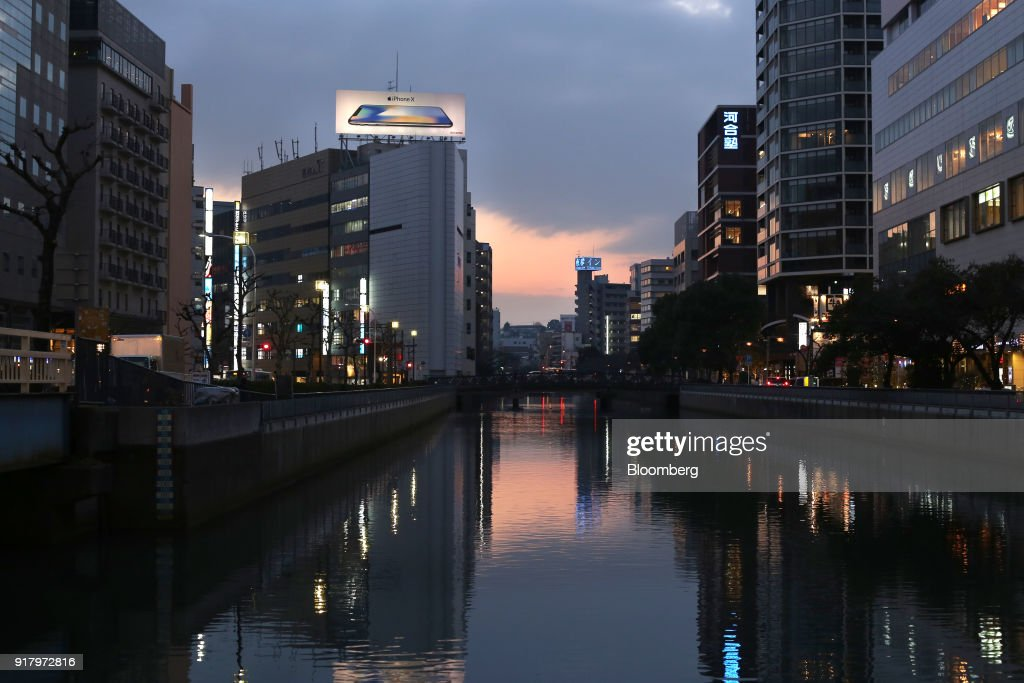 An advertisement for the Apple Inc. iPhone X smartphone is displayed atop a commercial building standing near the Katabira River in Yokohama, Japan, on Saturday, Feb. 3, 2018. Japans economy expanded for an eighth quarter, with its gross domestic product(GDP) grew at an annualized rate of 0.5 percent in the three months ended Dec. 31, but the pace of growth fell sharply and missed expectations. Photographer: Takaaki Iwabu/Bloomberg via Getty Images