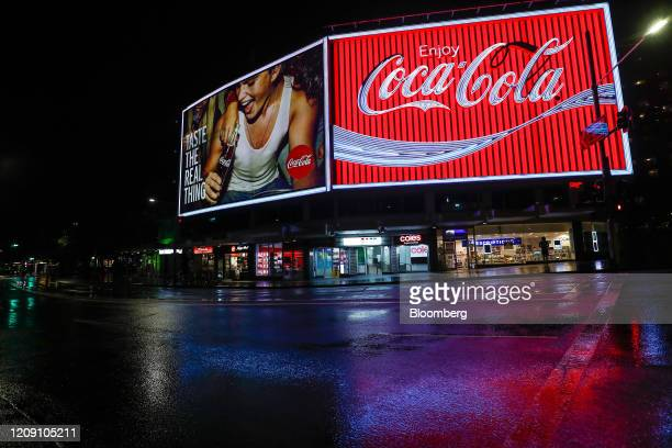 An advertisement for The Coca Cola Co. Stands illuminated at night during a partial lockdown imposed due to the coronavirus, at night in Sydney,...
