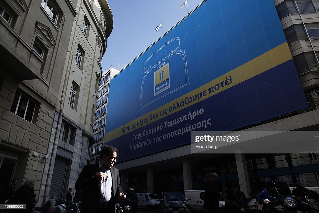 An advertisement hangs outside the offices of the Hellenic Postbank SA in Athens, Greece, on Tuesday, Jan. 22, 2013. Euro-area finance ministers blessed the next disbursement of emergency aid for Greece, highlighting the goodwill that led to the unblocking of loans last month for Prime Minister Antonis Samaras's government. Photographer: Kostas Tsironis/Bloomberg via Getty Images
