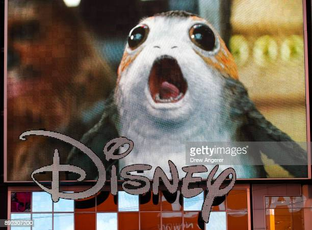 An advertisement of the new Star Wars film plays on a screen as the Disney logo is displayed outside the Disney Store in Times Square December 14...