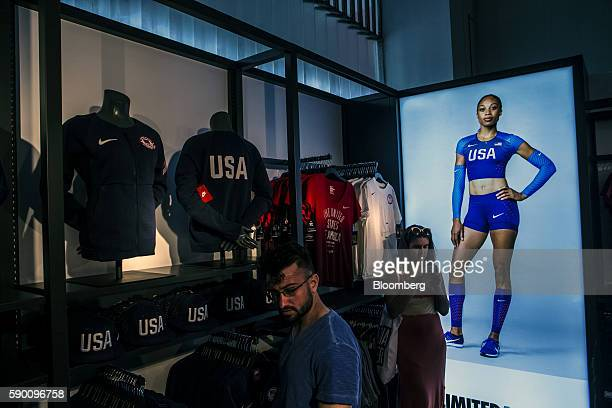 An advertisement with US Olympic track and field athlete Allyson Felix is displayed next to Nike Inc apparel for sale at the Team USA Shop in the...