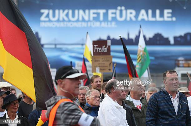 An advertising billboard reads 'Future for all' behind supporters of the Pegida movement listening to speakers during their weekly gathering on July...