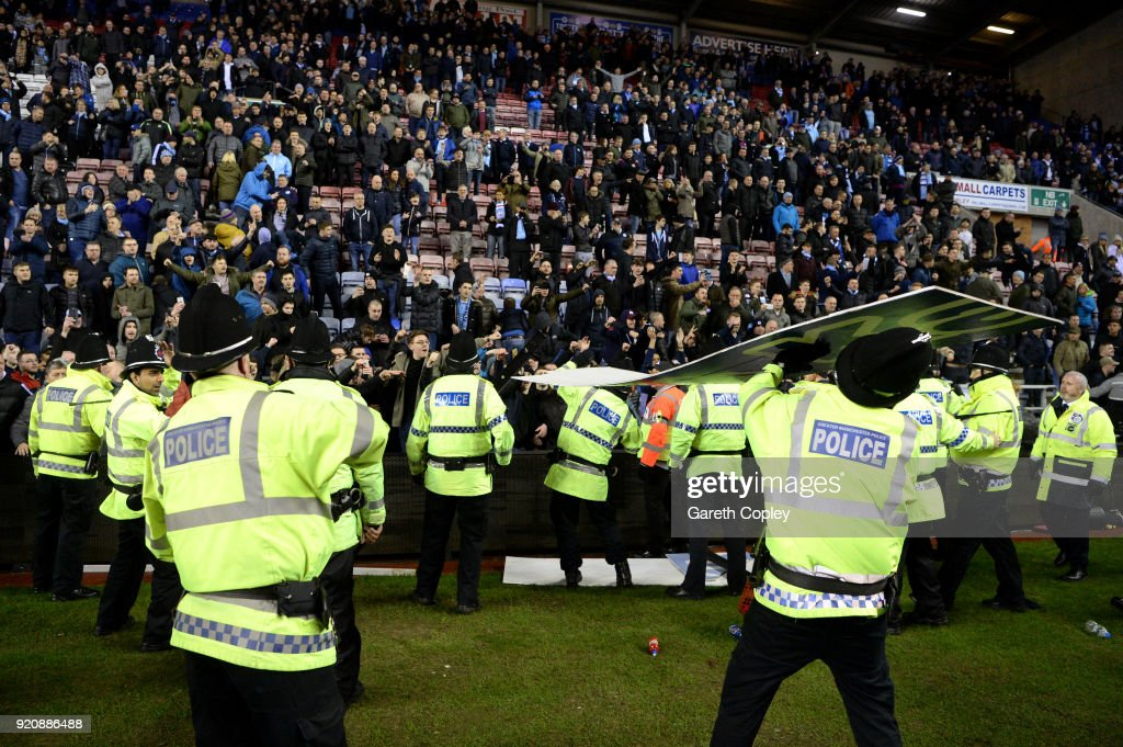 An advertising board is thrown at police as they attempt to prevent a pitch invasion after the Emirates FA Cup Fifth Round match between Wigan Athletic and Manchester City at DW Stadium on February 19, 2018 in Wigan, England.