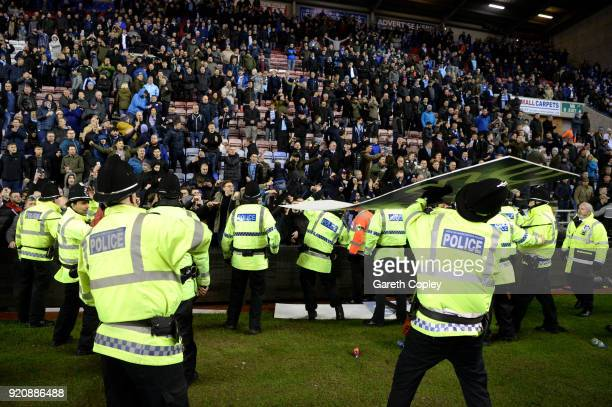 An advertising board is thrown at police as they attempt to prevent a pitch invasion after the Emirates FA Cup Fifth Round match between Wigan...