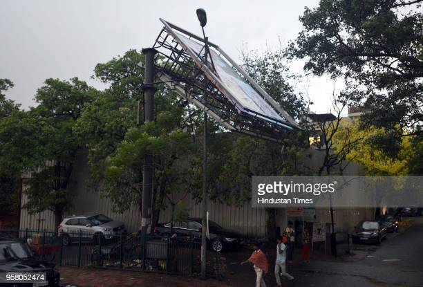 An advertising hording broke after sudden thunderstorm and duststorm at Defence Colony on May 13 2018 in New Delhi India Strong wind accompanied by...