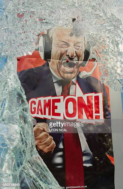 An advertising poster for a bookmaker is seen through smashed glass on High Road in Tottenham north London on August 7 2011 Two police cars and a...