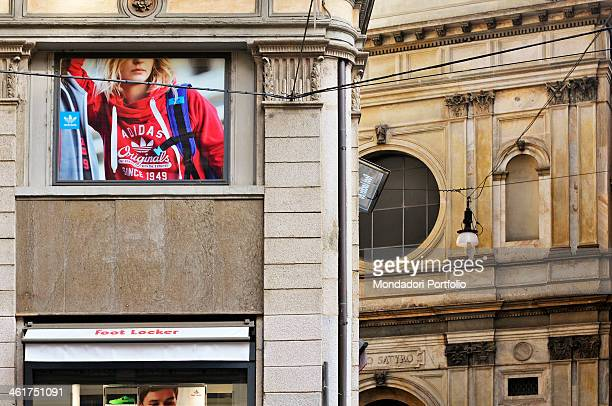 An advertising poster of Adidas sport clothes the Foot Locker shop in via Torino and the facade of Santa Maria presso San Satiro Milan Italy 2013