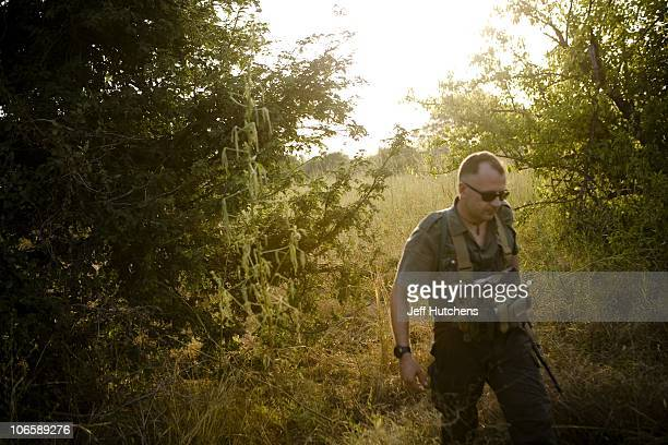 An advisor to antipoaching squads marches through the brush steps away from an elephant lying dead in the grasslands of Zakouma National Park under...