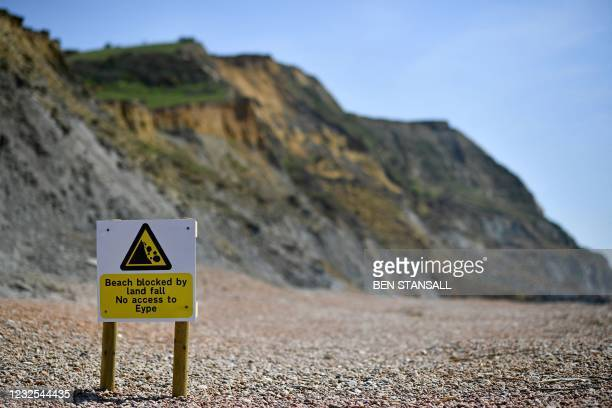 An advisory notice is seen on the beach close to the scene of a coastal cliff fall on Dorset's Jurassic Coast near the village of Seatown, on the...