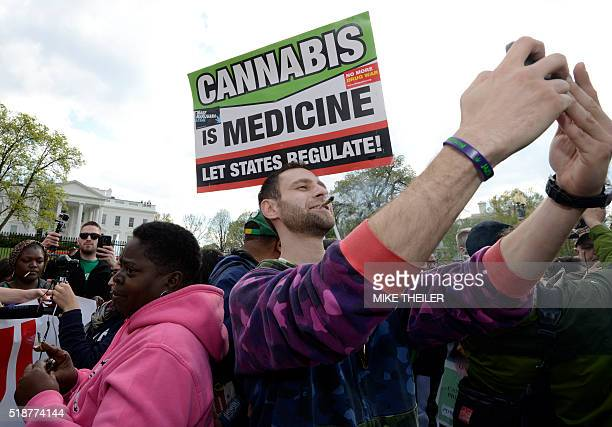 An advocate for the legalization of marijuana takes a 'selfie' after lighting up in front of the White House during a demonstration by dozens who...