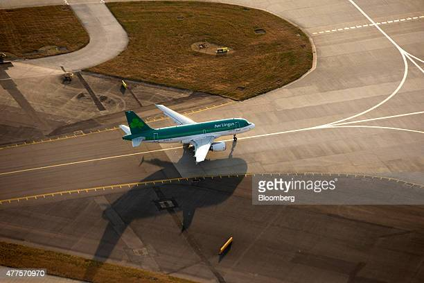 An Aer Lingus aircraft operated by Aer Lingus Group Plc stands on the perimeter of the runway at London Heathrow Airport in this aerial photograph...
