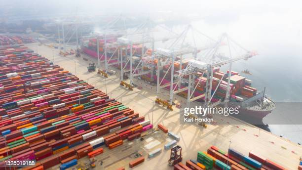 an aerial daytime view of a container ship being loaded in port, uk - stock photo - harbour stock pictures, royalty-free photos & images