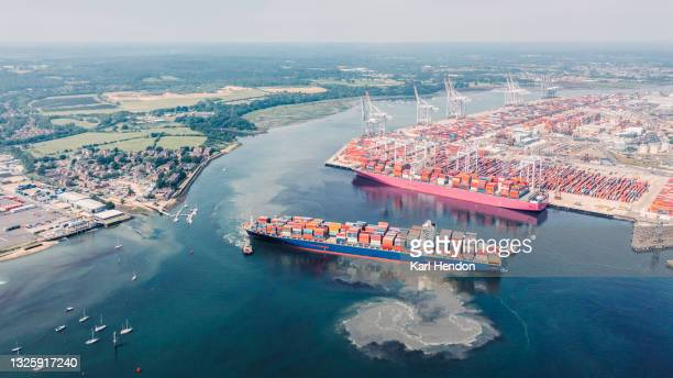 an aerial daytime view of a container ship being turned 180 degrees by tug boats in a uk port - stock photo - southampton england stock pictures, royalty-free photos & images