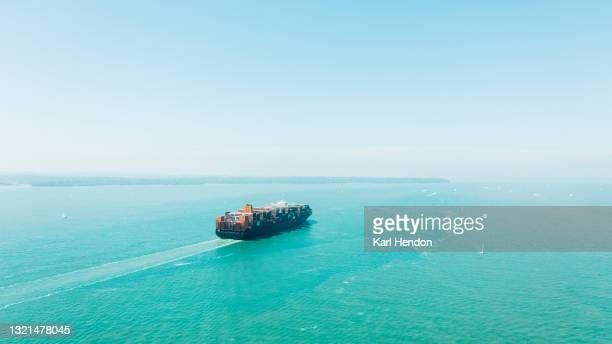 an aerial daytime view of a container ship on the solent sea, uk - stock photo - portsmouth england stock pictures, royalty-free photos & images