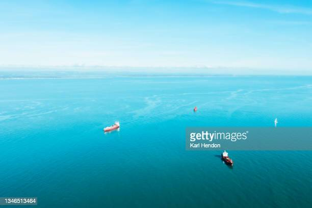 an aerial daytime view of oil tankers on the solent sea, uk - stock photo - portsmouth england stock pictures, royalty-free photos & images