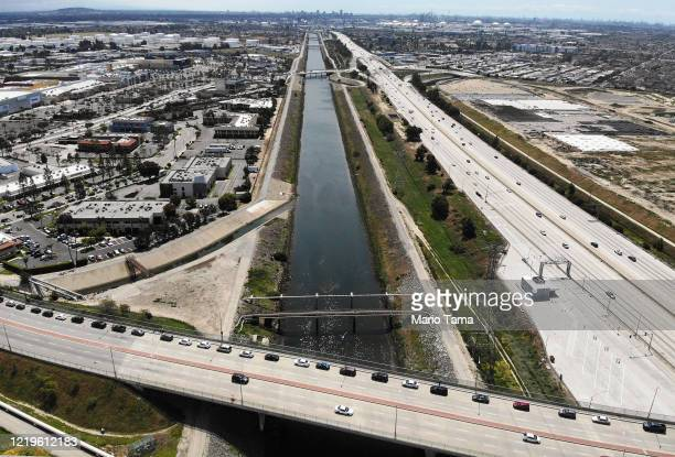 An aerial drone view of cars lined up to receive food distributed by the Los Angeles Regional Food Bank with light traffic on the 405 freeway below...
