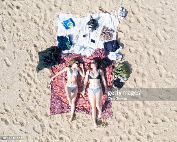 An aerial drone view of Karla and Jemima sunbathing at Bournemouth Beach on March 30,2021 in Bournemouth, England. Weather is expected to become...