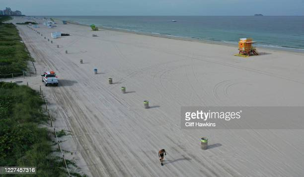 An aerial drone view shows Robert Raven Kraft running alone on the closed beach after being granted special permission by city officials on May 27...