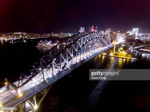 an aerial image of the sydney harbour bridge at night. - david ewing stock pictures, royalty-free photos & images