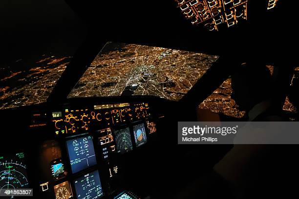 An aerial night view of London from an airliner flight deck.