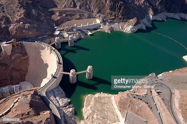 An aerial photo of Hoover Dam with the Lake Mead reservoir behind The white lines along the shore indicate the dropping water level of the reservoir...