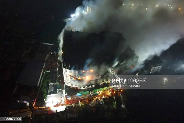 An aerial photo show firefighters trying to extinguish a massive fire that broke out in a beverage and food factory in Narayanganj, central...