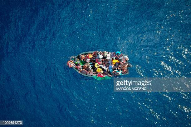 TOPSHOT An aerial photo shows a boat carrying migrants stranded in the Strait of Gibraltar before being rescued by the Spanish Guardia Civil and the...