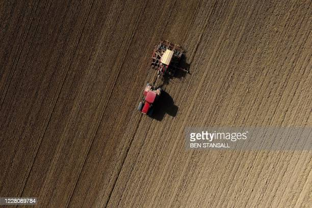 An aerial photo shows a farmer using a tractor and a seed drill to sow seeds for crops in Brenchley, south-east England on August 18, 2020.