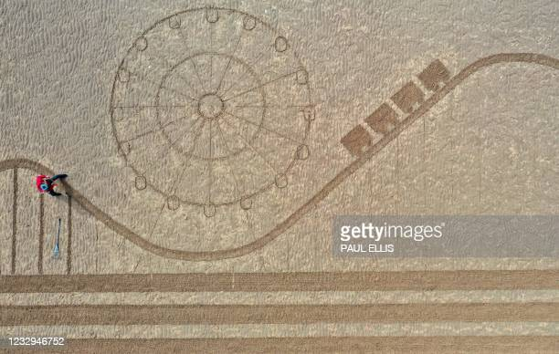 An aerial photo shows a piece of sand art, depicting the iconic Tower, Pier, and rides of Blackpool in north west England, drawn in the sand on the...
