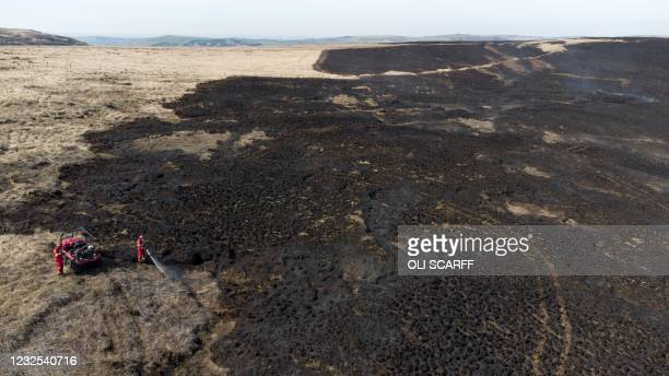 An aerial photo shows firefighters using a low ground pressure vehicle to monitor and tackle any resurgence of a moor fire on Marsden Moor, near...