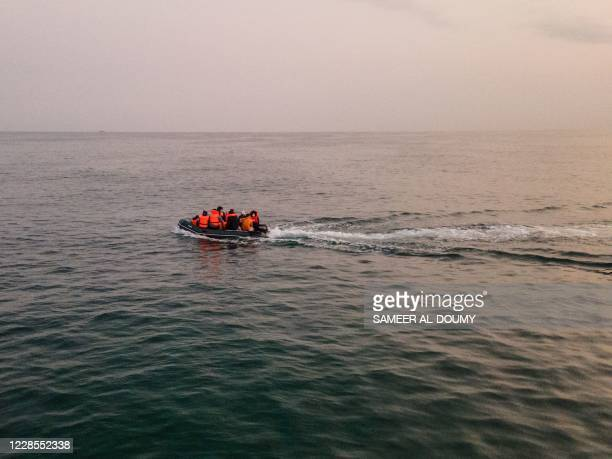 An aerial photo shows migrants in a dinghy wearing life jackets as they illegally cross the English Channel from France to Britain on September 11,...