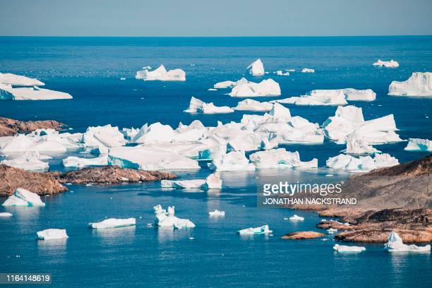 An aerial photo taken on August 15, 2019 shows icebergs as they float along the eastern cost of Greenland near Kulusuk .