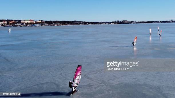 An aerial photo taken on February 28, 2021 shows ice surfers skating across the frozen Baltic Sea off the coast of Helsinki. - What to do if you are...