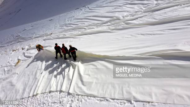 An aerial photo taken on June 19, 2020 shows workers covering with huge geotextile sheets the Presena glacier on the Val di Sole near Pellizzano in...