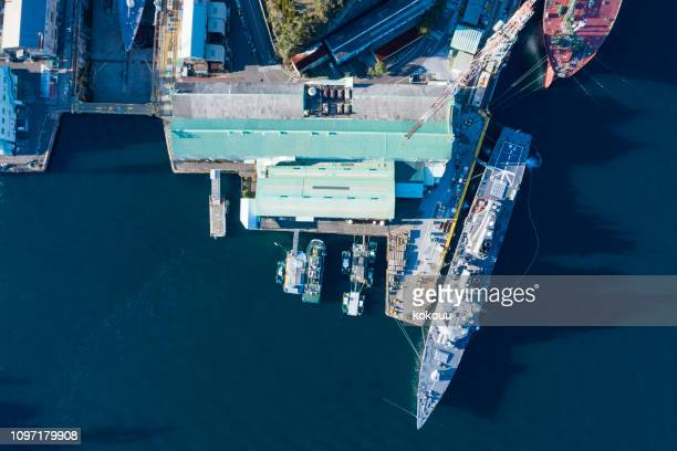 an aerial photograph of a battleship at a berth and a factory along the sea. - moored stock pictures, royalty-free photos & images