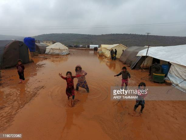 An aerial photograph shows children playing near tents sheltering Syrians who fled ongoing battles in the southern and eastern coutryside of the...
