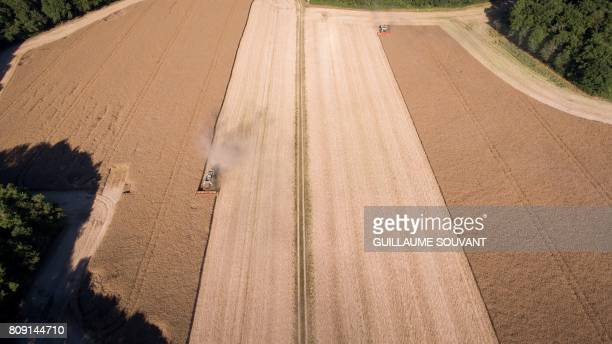 An aerial picture shows a combine harvester during a rape harvest on July 4 2017 near Monthodon central France
