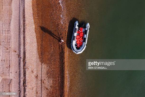 An aerial picture shows a man using a mobile telephone whilst standing next to a recently abandoned inflatable boat, used by migrants to cross the...