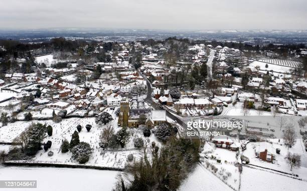 An aerial picture shows All Saints Church and the village of Brenchley beyond, shrouded in snow, in the south east of England on February 8, 2021. -...