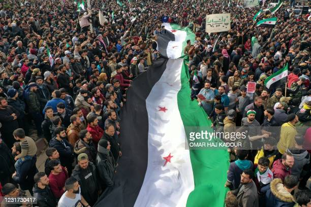 An aerial picture shows Syrians waving the opposition flag during a gathering in the rebel-held city of Idlib on March 15 as they mark ten years...