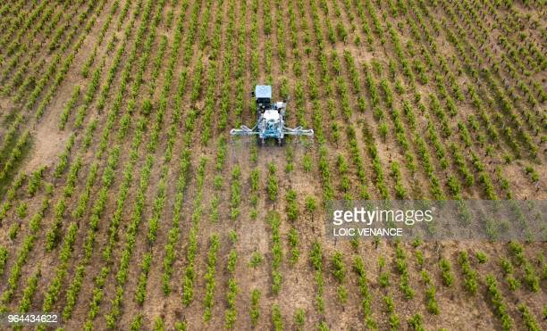 An aerial picture taken on April 26, 2018 shows a farmer spraying chemicals to treat vineyard in Vertou, outside Nantes, western France.