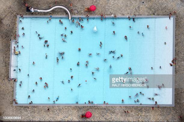 TOPSHOT An aerial picture taken on August 1 2018 shows people swimming at the Kiebitzberge public outdoor swimming pool on a warm summer day in...