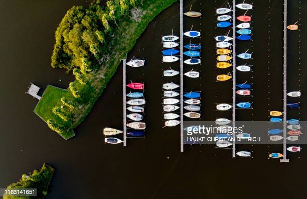 TOPSHOT An aerial picture taken on August 21 2019 shows sailboats at a marina on the lake Zwischenahner Meer in Bad Zwischenahn near Oldenburg...