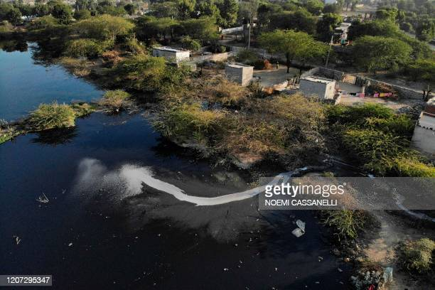An aerial picture taken on December 30, 2019 shows waste from textile factories released inside a river in Sanganer village on the outskirts of...