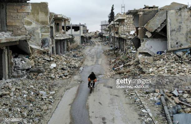 An aerial picture taken on February 15 shows a Syrian man on a motorbike in the deserted Syrian city of Kafranbel, south of Idlib city in the...